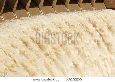 Strong flowing water released from the open sluice gates of a large dam