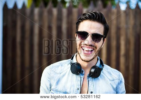 Portrait of a young handsome man with toupee and headphones in urban background