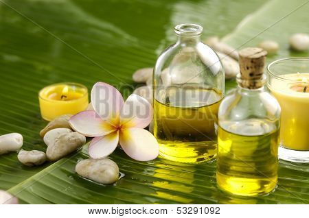 frangipani and stones with yellow candle, massage oil  on wet banana leaf