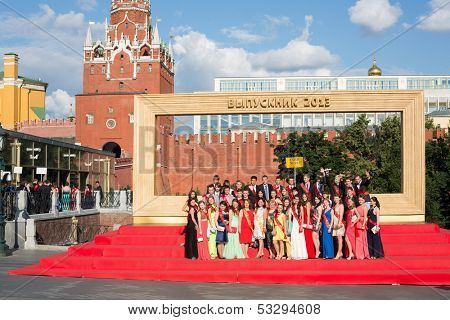 MOSCOW - JUN 23: Graduates are photographed in front of big frame on Sapozhkovaya Square near the Kremlin on June 23, 2013 in Moscow, Russia.