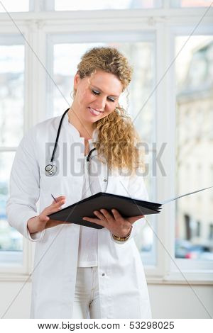 Young female doctor sitting on a desk in front of window in clinic with test results in a file or dossier