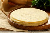 stock photo of flat-bread  - stack of corn tortillas on a wooden plate - JPG
