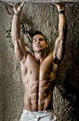 picture of shirtless  - Handsome muscular man shirtless wearing white pants arms up in front of concrete wall - JPG