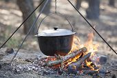 stock photo of dutch oven  - Camping kettle over burning campfire in forest - JPG