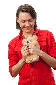 stock photo of gey  - Young guy with his loved from childhood toy  - JPG