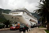 KOTOR, MONTENEGRO - CIRCA MAY 2010 - Big cruise ship departs in a small harbor