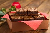 picture of brownie  - Freshly baked brownies in a brown paper box with red napkin with red rose in the back (Selective Focus Focus on the upper left brownie)