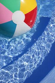 stock photo of beach-ball  - Multicolored Beachball in a beautiful blue swimming pool - JPG