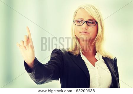 Young beautiful businesswoman making choise on abstract screan