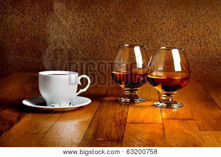 Two Goblets Of Brandy And Cup Of Hot Coffeeon Wooden Old Counter Top