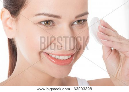 Young beautiful cleaning face with cotton pads. Isolated on white.