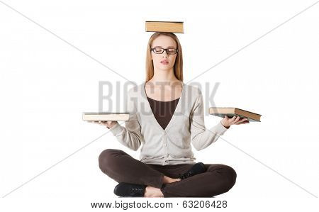 Beautiful casual woman sitting with books on palms and head, doing yoga. Isolated on white.