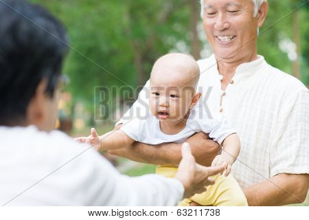 Asian grandparents playing with baby grandson at outdoor garden.