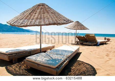 Sunbeds And Rattan Parasols On Sandy Seaside.