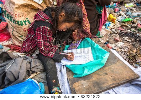 KATHMANDU, NEPAL - DEC 19, 2013: Unidentified child is sitting while her parents are working on dump. In Nepal 50,000 children annually die, in 60% of cases -malnutrition.