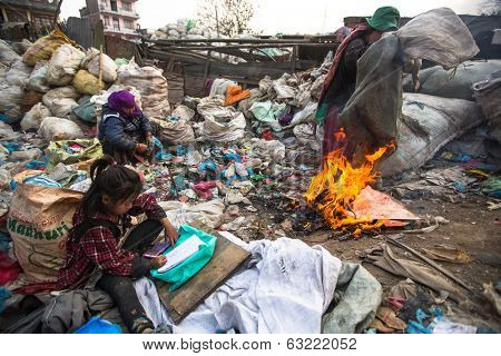 KATHMANDU, NEPAL - DEC 19, 2013: Unidentified child is sitting while her parents are working on dump. In Nepal annually die 50,000 children, in 60% of cases -malnutrition.