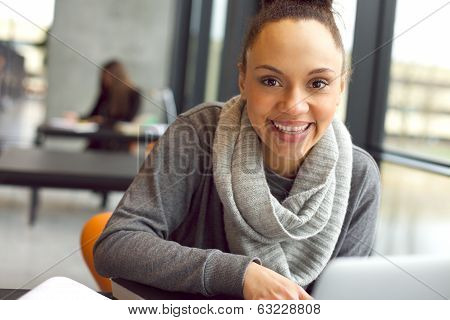 Cheerful Young Woman Sitting In Library