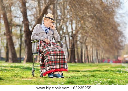 Grumpy old man sitting in a wheelchair outdoors