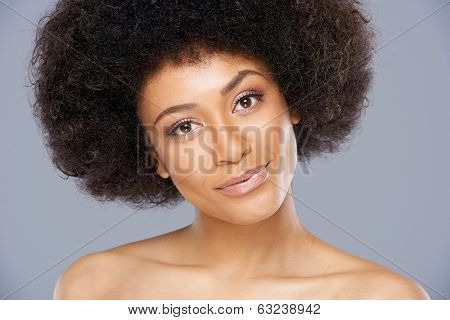 Pretty African American woman with a lovely smile and a cute frizzy afro hairstyle standing with bare shoulders smiling at the camera
