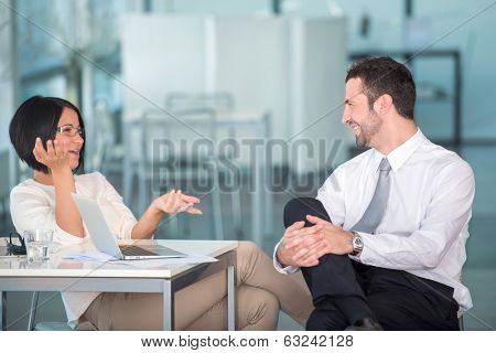 Two colleagues talking relaxed in office