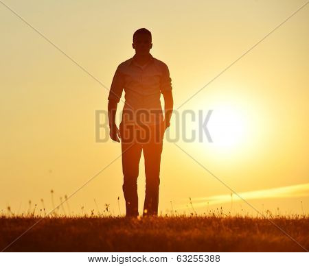 Man walking on summer sunset meadow
