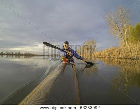 senior male paddler enjoys morning workout in a slim racing kayak on a calm lake in Colorado
