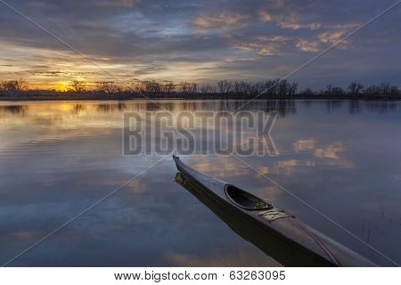a slim sea kayak ready for paddling workout before sunrise on a calm lake in Colorado