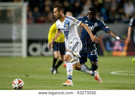 CARSON, CA - APRIL 12: Los Angeles Galaxy M Marcelo Sarvas #8 & Vancouver Whitecaps F Kekuta Manneh #23 during the MLS game between the Los Angeles Galaxy & the Vancouver Whitecaps on April 12th 2014