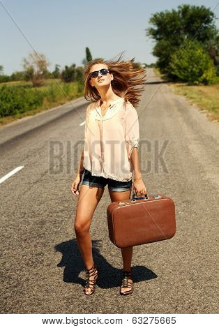 Pretty Young Woman With Suitcase, Hitchhiking Along A Countryside Road