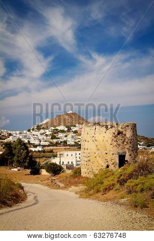 Traditionnal old windmill with plaka city in background on Milos Island, Greece