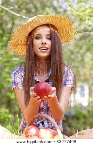 Smiling Young Woman Eating Organic Apple in the Orchard.Basket of Apples.
