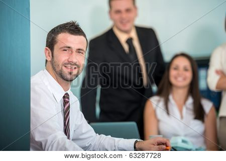 Smling businessman sitting in office posing