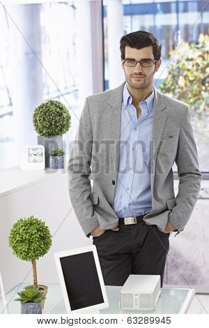 Handsome businessman standing in office with hands in pocket, looking away.