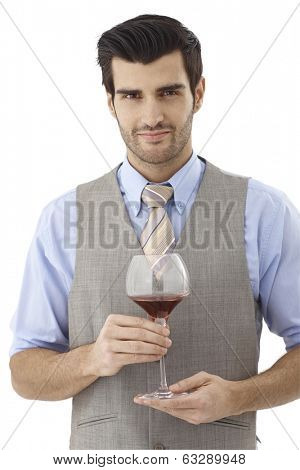 Portrait of happy young man holding glass of red wine, looking at camera.
