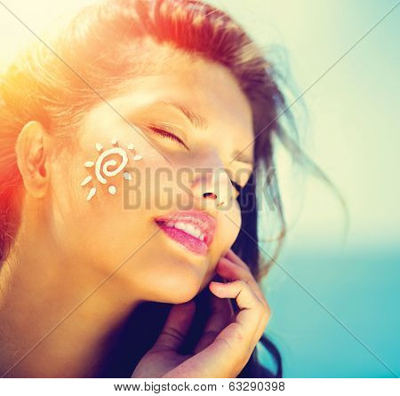 Suntan Lotion Woman Applying Sunscreen Solar Cream. Beautiful happy cute Girl applying Sun Tan Cream on her Face over ocean background. Sun Tanning. Skin care and Protection. Vacation