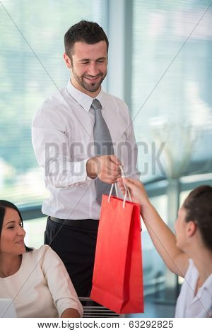 Happy business man giving a gift to female coworker