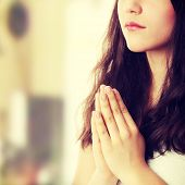 stock photo of kneeling  - Closeup portrait of a young caucasian woman praying - JPG