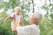 stock photo of grandpa  - Asian Chinese grandpa and grandson having fun at outdoor garden - JPG