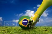 soccer player foot hitting a ball with Brazilian flag wrapped on it