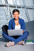 cheerful african college student using laptop