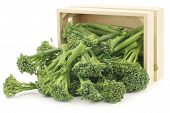 A small form of broccoli, called bimi, in a wooden box on a white background
