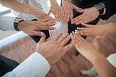 People joning hands together in office environment
