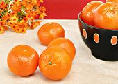 picture of clementine-orange  - Organic clementines on a table with a full bowl of orange fruit to the side - JPG