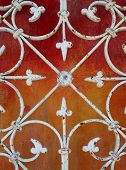 pic of wrought iron  - Wrought iron webbing against red and orange plaster wall - JPG