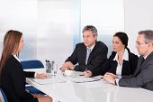 stock photo of interview  - Group Of Businesspeople Interviewing Woman In Office - JPG