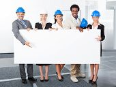 picture of placard  - Group Of Happy Multiracial Architects Holding Placard In Office - JPG