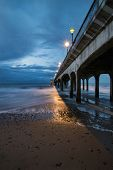 stock photo of moonlight  - Twilight landscape of pier stretching out into sea with moonlight