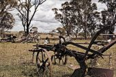 picture of horse plowing  - an old rusting horse drawn plow and machinery sits in the farm paddock - JPG