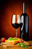 picture of lasagna  - traditional lasagna bolognese meal with glass and bottle of red wine - JPG