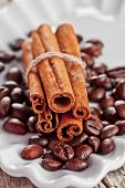 stack of cinnamon sticks and coffee beans in white plate